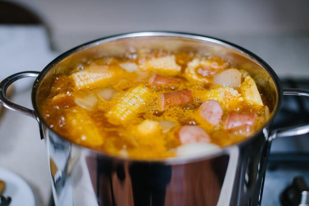 corn boiling in large pot with potatoes, onion and lemon