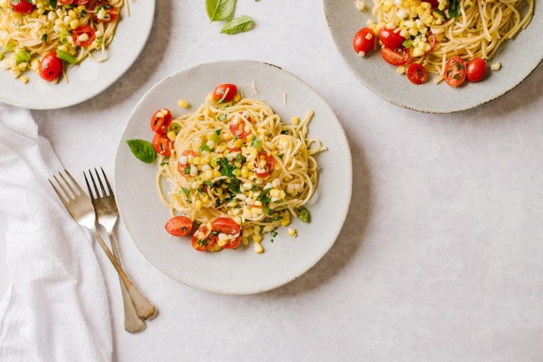 A plate of Pasta with Sweet Corn Gremolata and two forks on the side with two plates of pasta just out of frame