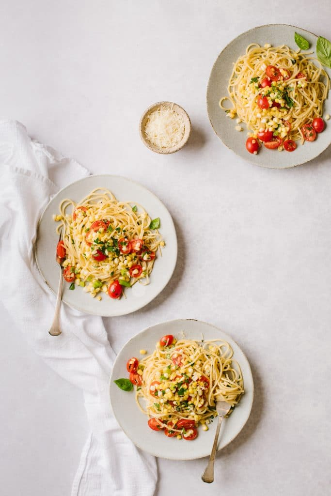 three plates of pasta with sweet corn gremolats and a small bowl of Parmesan