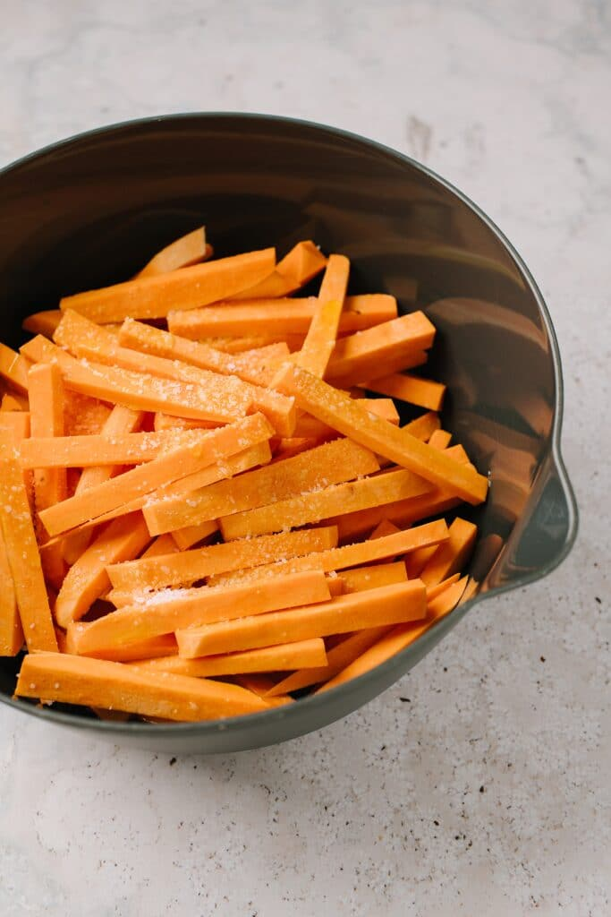 unbaked sweet potato fries in large bowl