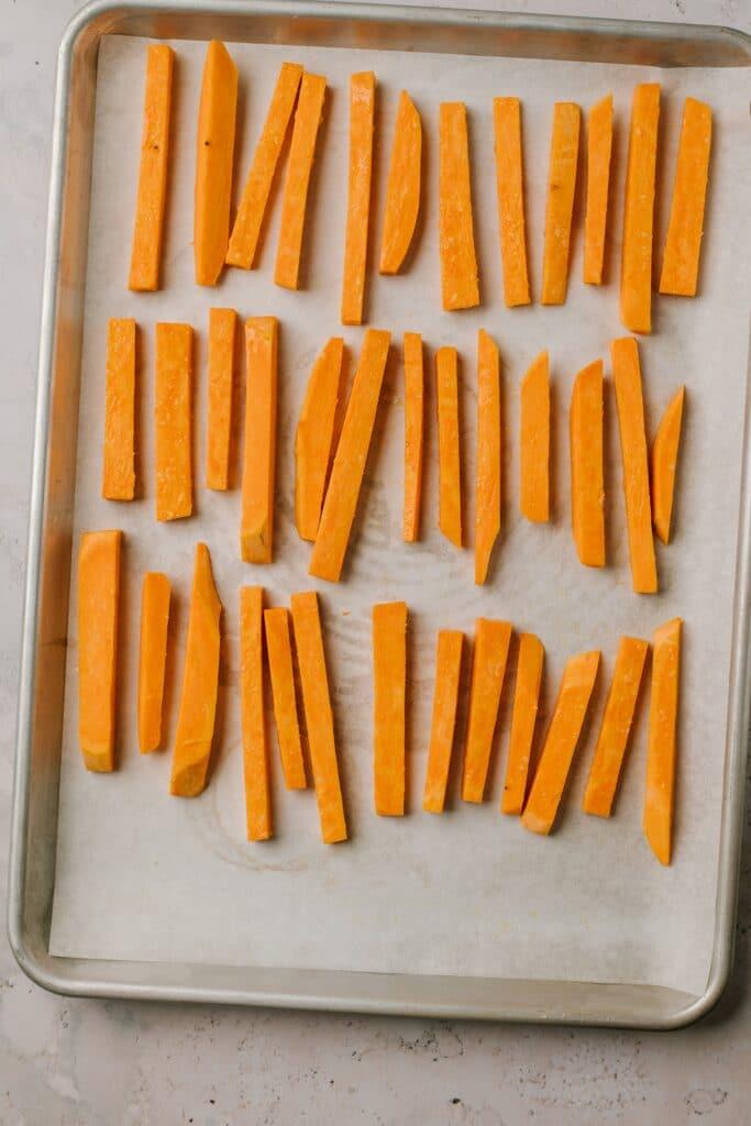 sweet potato batons lined up on baking sheet