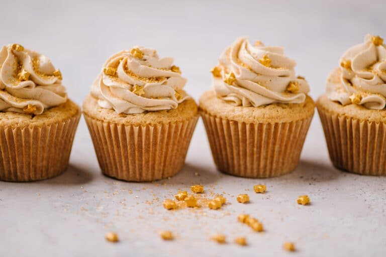 line of biscoff cupcakes with buttercream and gold star sprinkles