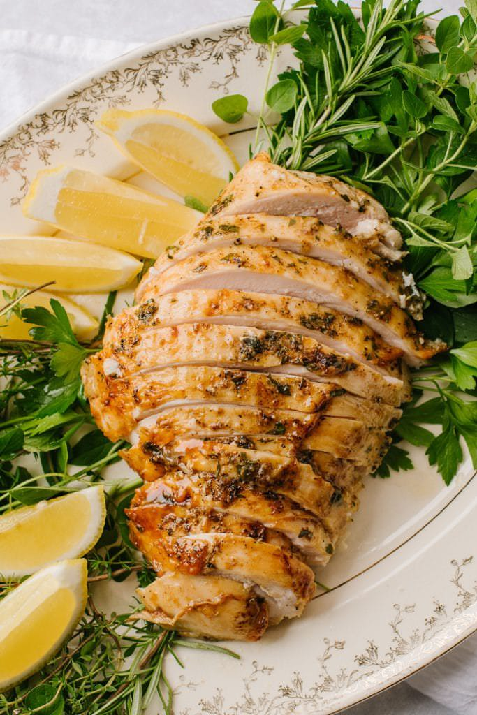 easy brined turkey breast sliced on white platter with lemon wedges and fresh herbs