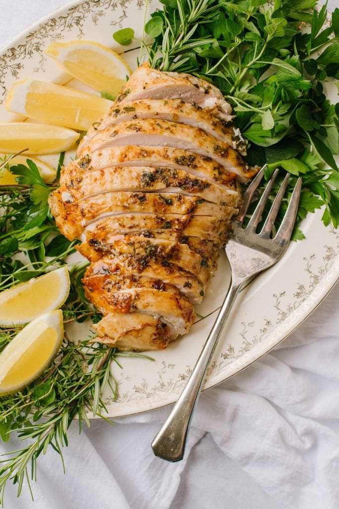 sliced turkey breast on white platter with lemon wedges, fresh herbs and fork
