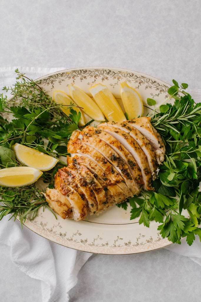 best brined turkey sliced on white platter with lemon wedges and fresh herbs
