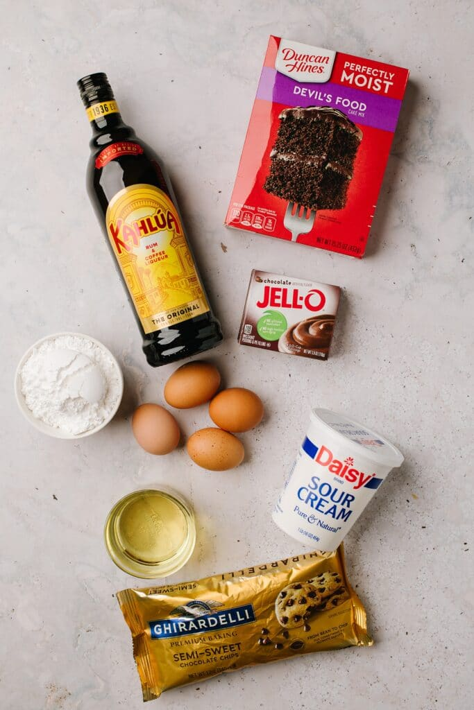 boxed cake mix, kahlua, instant chocolate pudding mix, eggs, sour cream, oil, powdered sugar, semiisweet chocolate chips