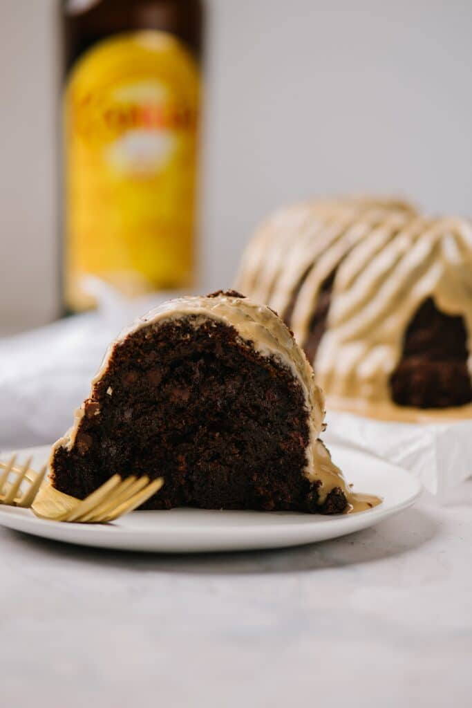 slice of chocolate cake with kahlua glaze on white plate with kahlua bottle and cake in background