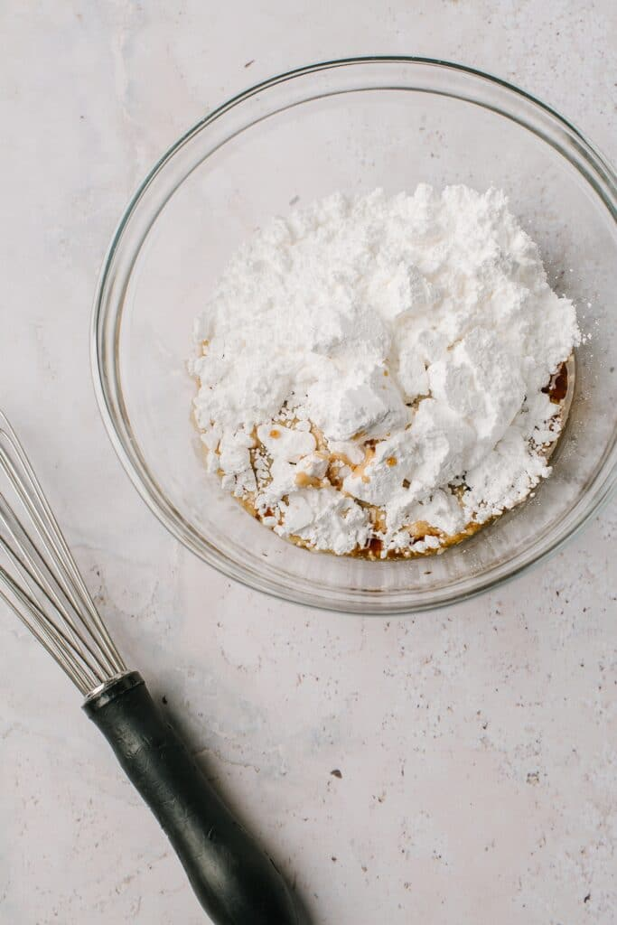powdered sugar and kahlua in glass bowl with whisk
