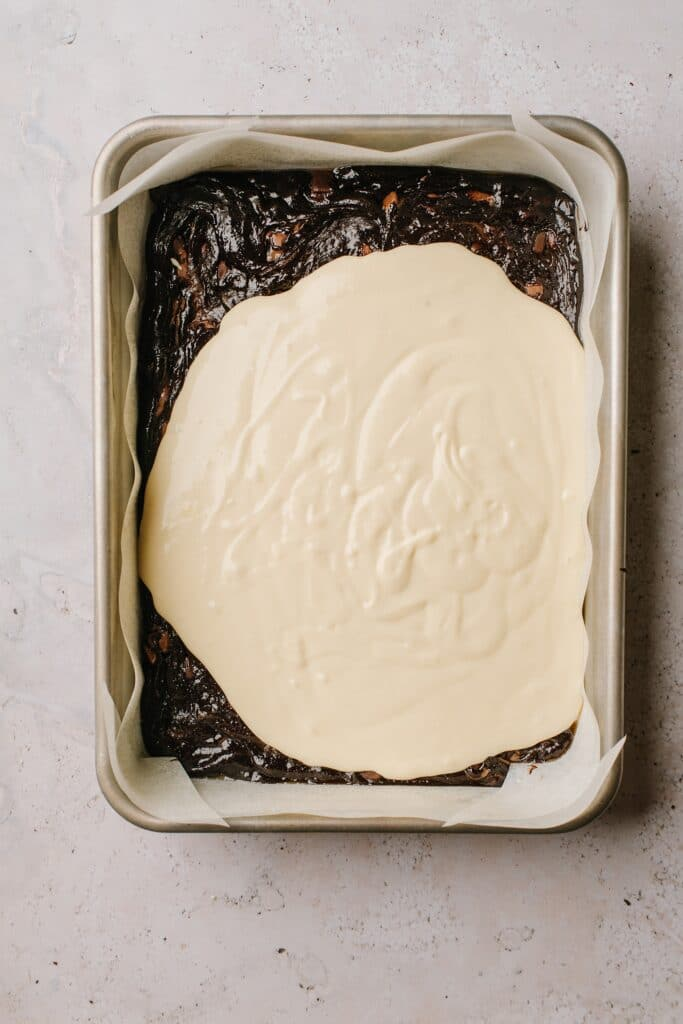 cheesecake batter spread over brownie batter in baking dish