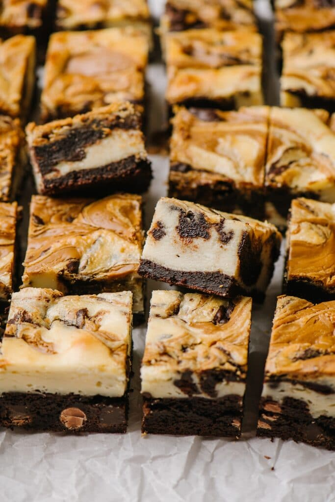 cream cheese brownie squares on parchment paper