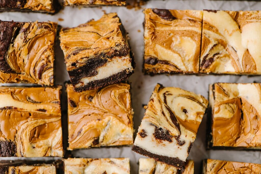 overhead shot of cookie butter cheesecake brownies with two turned on side