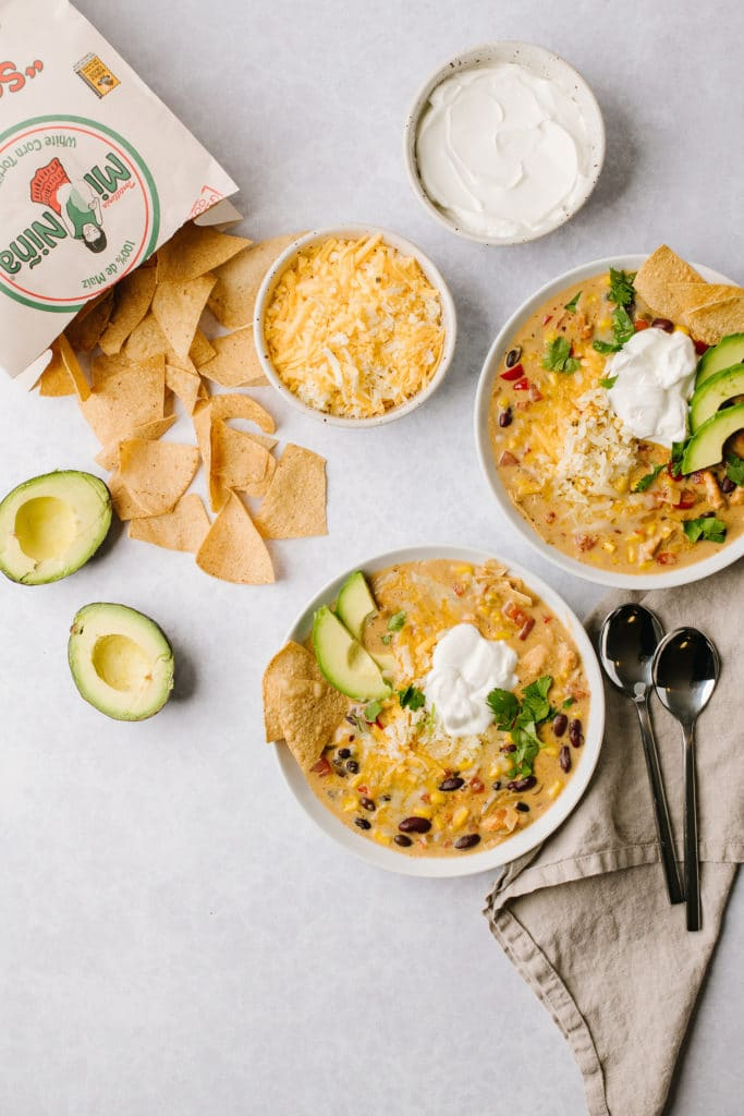 two bowls of creamy chicken tortilla soup with spoons with chips and sour cream on side