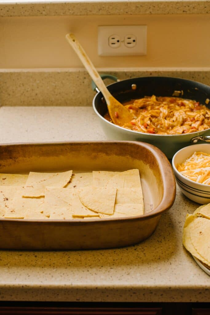 quartered corn tortillas in baking dish with chicken and tomato filling in skillet