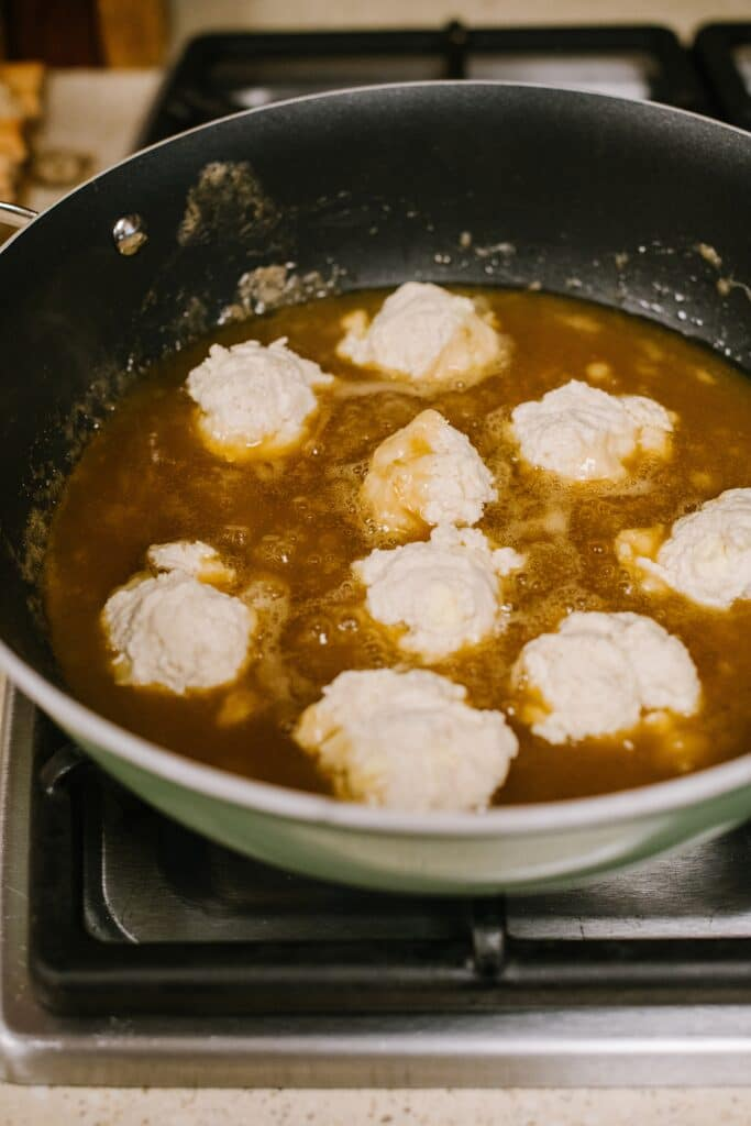 dumplings simmering in maple syrup sauce in skillet
