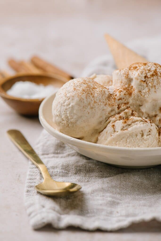 scoops of no churn ice cream recipe topped with cinnamon with cone in white bowl and spoon on side