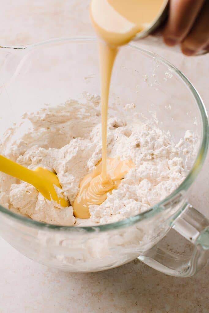 pouring sweetened condensed milk in whipped cream in glass bowl