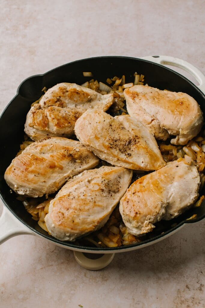 seared chicken breasts and onions in cast iron skillet