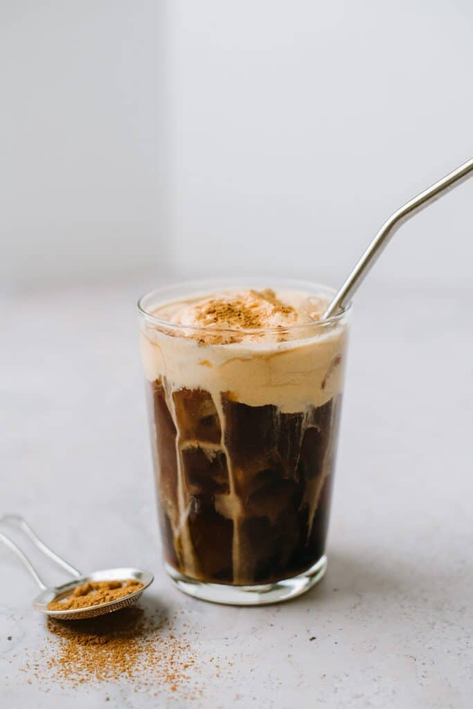 pumpkin cream cold brew in glass with metal straw