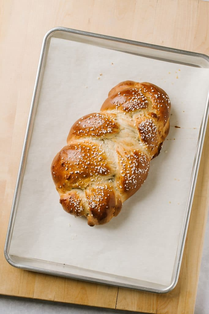 braided cardamom bread on parchment lined baking sheet
