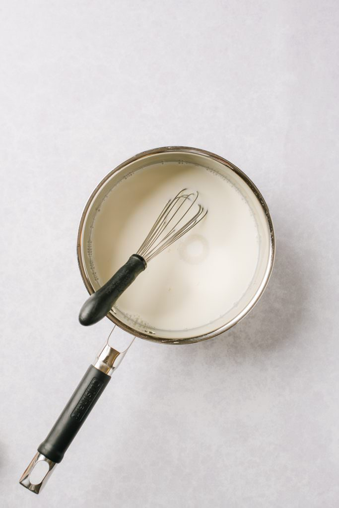 milk and sugar in pot with whisk