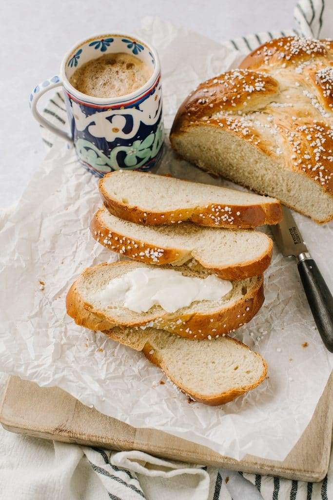 sliced cardamom bread slather with butter with cup of coffee