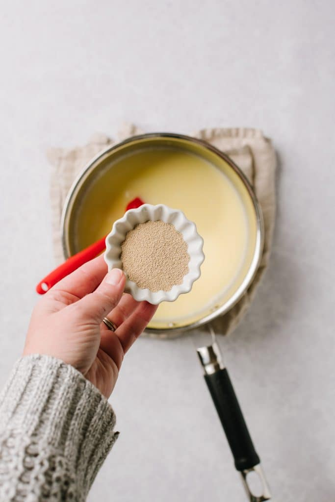 hand holding small bowl of yeast over warm milk and melted butter in pot
