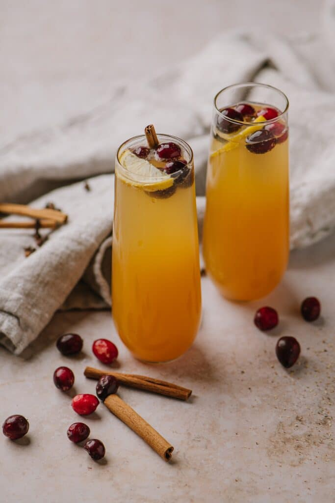 Spiced Apple Cider cocktails in another form, with champagne, topped with cranberries and orange