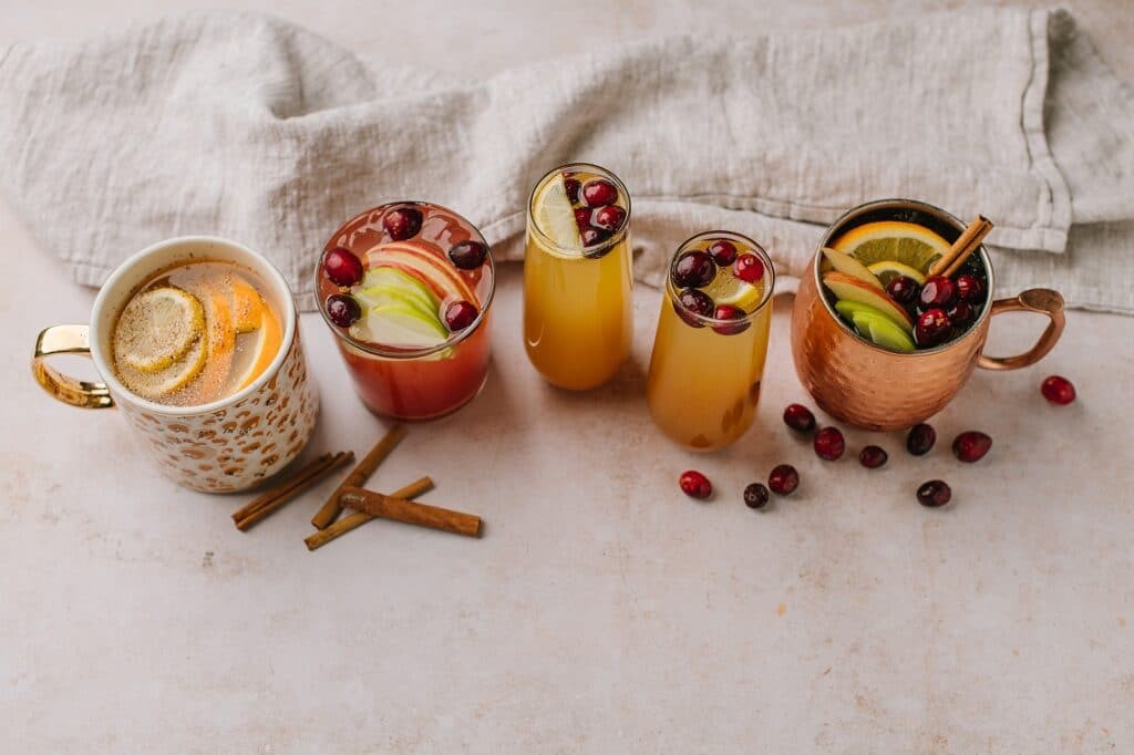 A shot with the multiple variations of spiced apple cider cocktails, both warm and chilled, with various types of garnishes and alcohol.