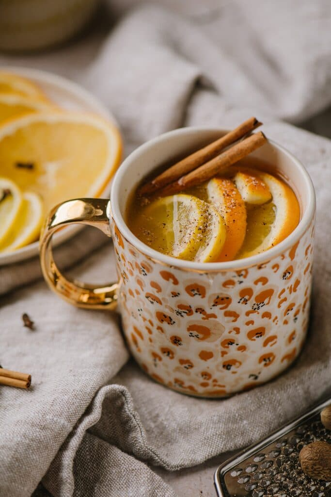 A traditional warm spiced apple cider, topped with cinnamon sticks and oranges. Sliced oranges on a plate are in the background.