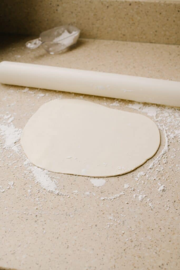 Sugar cookie dough, rolled out on a flour-coated surface, ready to be cut into shapes.