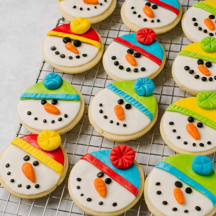 12 sugar cookies, decorated as snowmen, on a cooling rack.