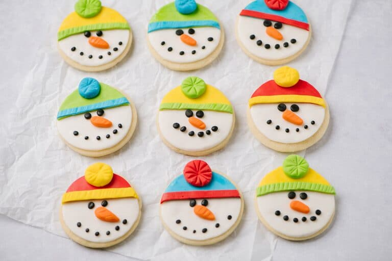 Nine sugar cookies shaped like snowmen faces, with different colored hats.