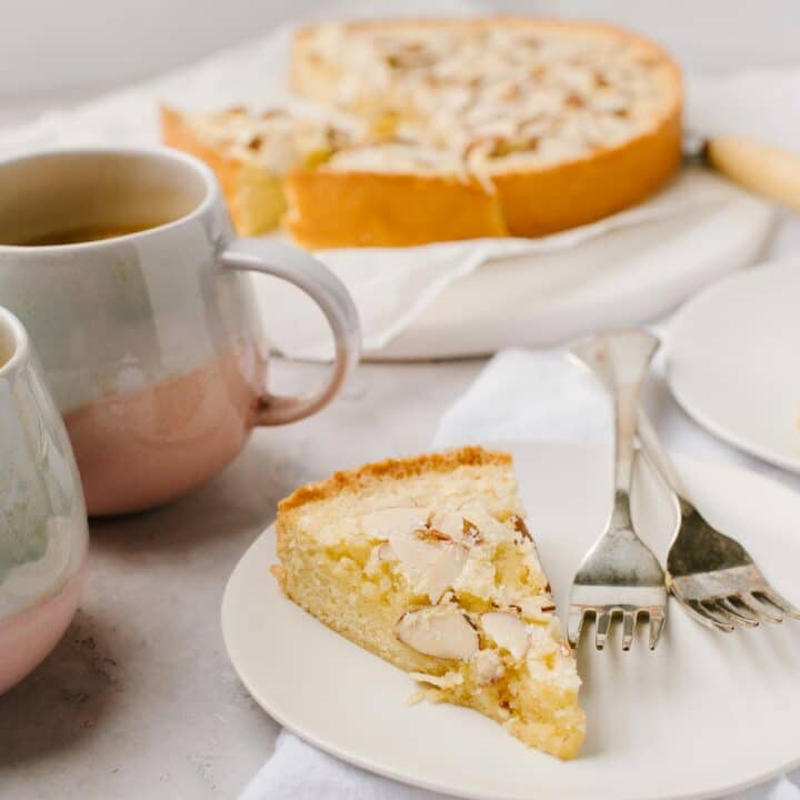 A slice of swedish visiting cake, with two mugs and the larger cake in the background.