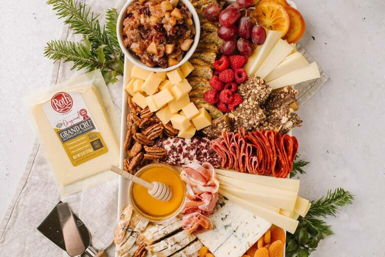 package of roth grand cru and cheese utensils next to a cheeseboard
