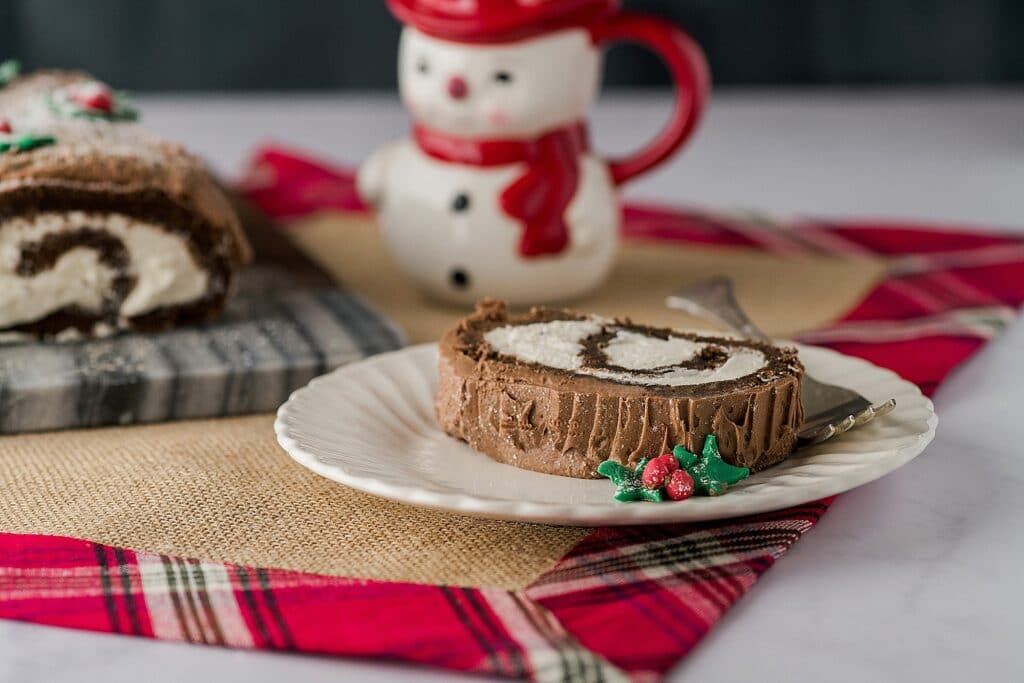 chocolate roll slice on a plate with a snowman mug in the background