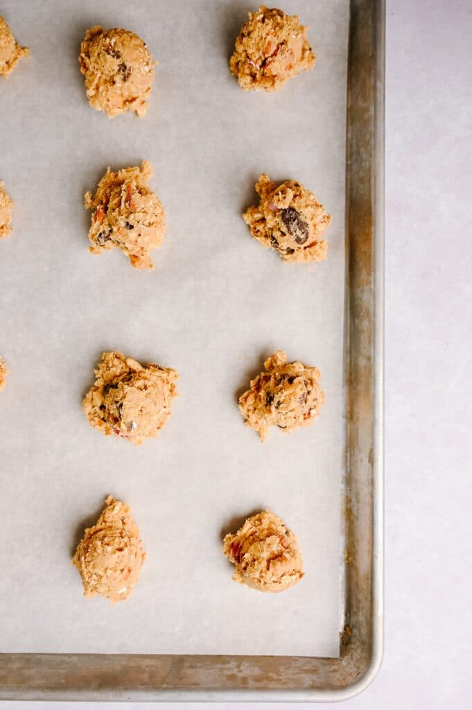 balls of Salted Peanut Butter Pretzel Cowboy Cookies dough on a sheet pan lined with parchment waiting to be baked