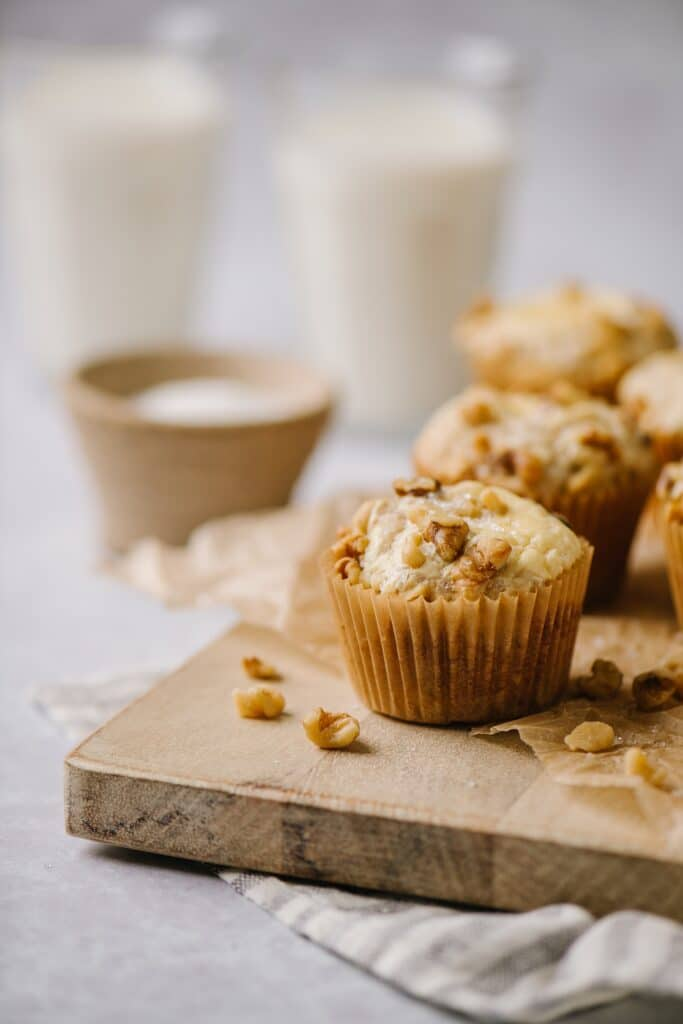 banana cream cheese muffins on a cutting board with milk in the background
