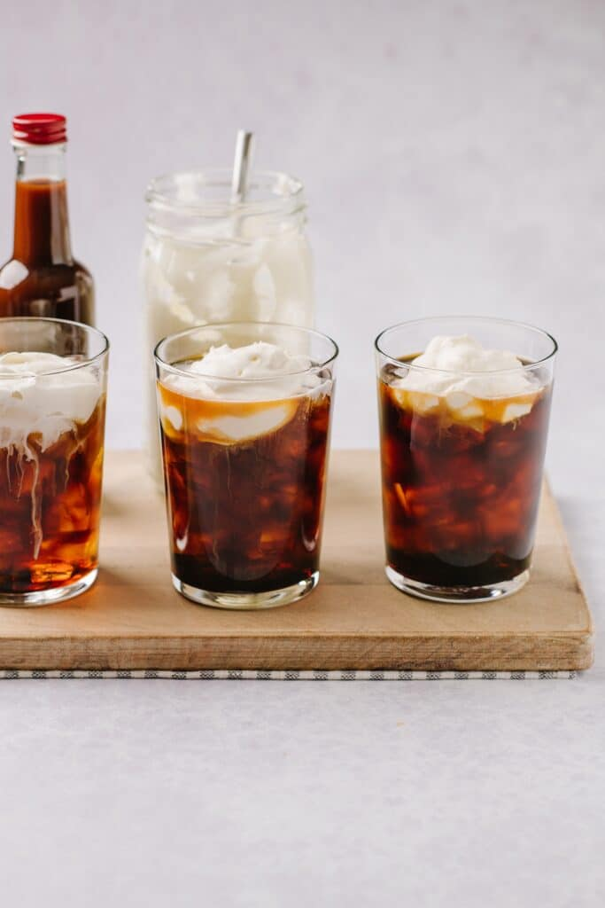 glasses of cold brew in a line with whipped cream on top