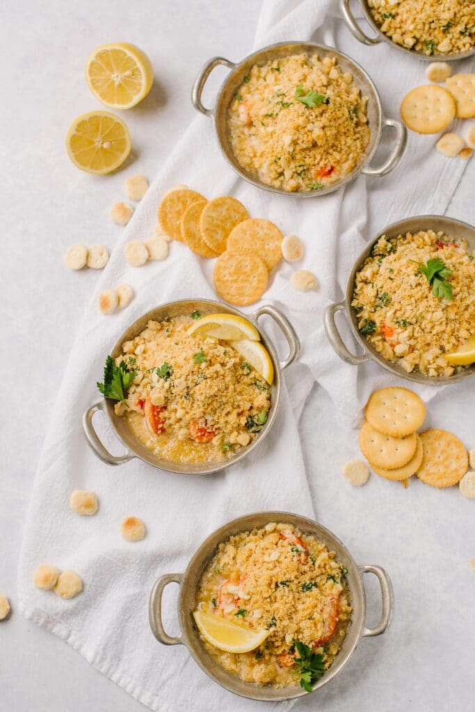 four dishes of lazy lobster casserole on a table with ritz crackers and lemon wedges