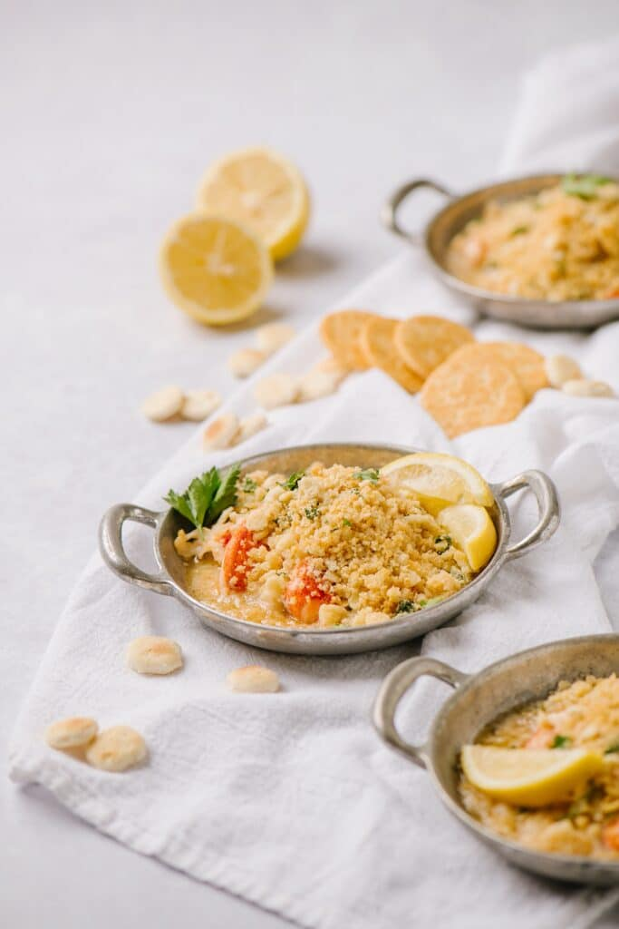 lazy lobster casserole dish with lemon wedges and Ritz crackers