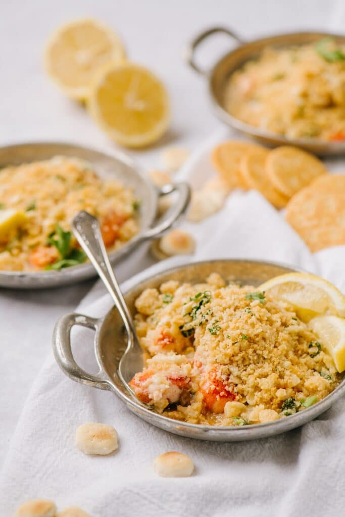 lobster casserole in three dishes with crackers and lemon wedges with a fork in one of them.