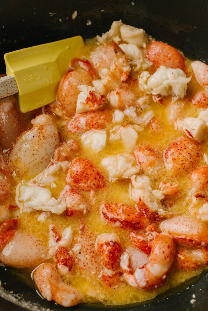 lobster being cooked in butter and garlic on the stove