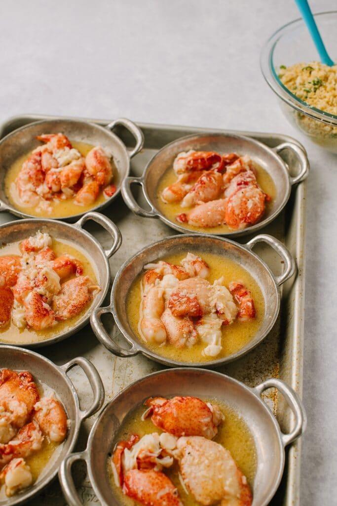 lobster in garlic sauce in individual ramekins on a baking sheet