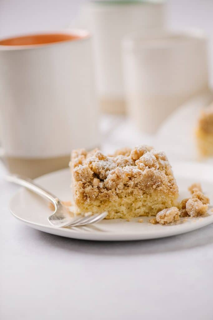 a piece of new york crumb cake on a plate with fork