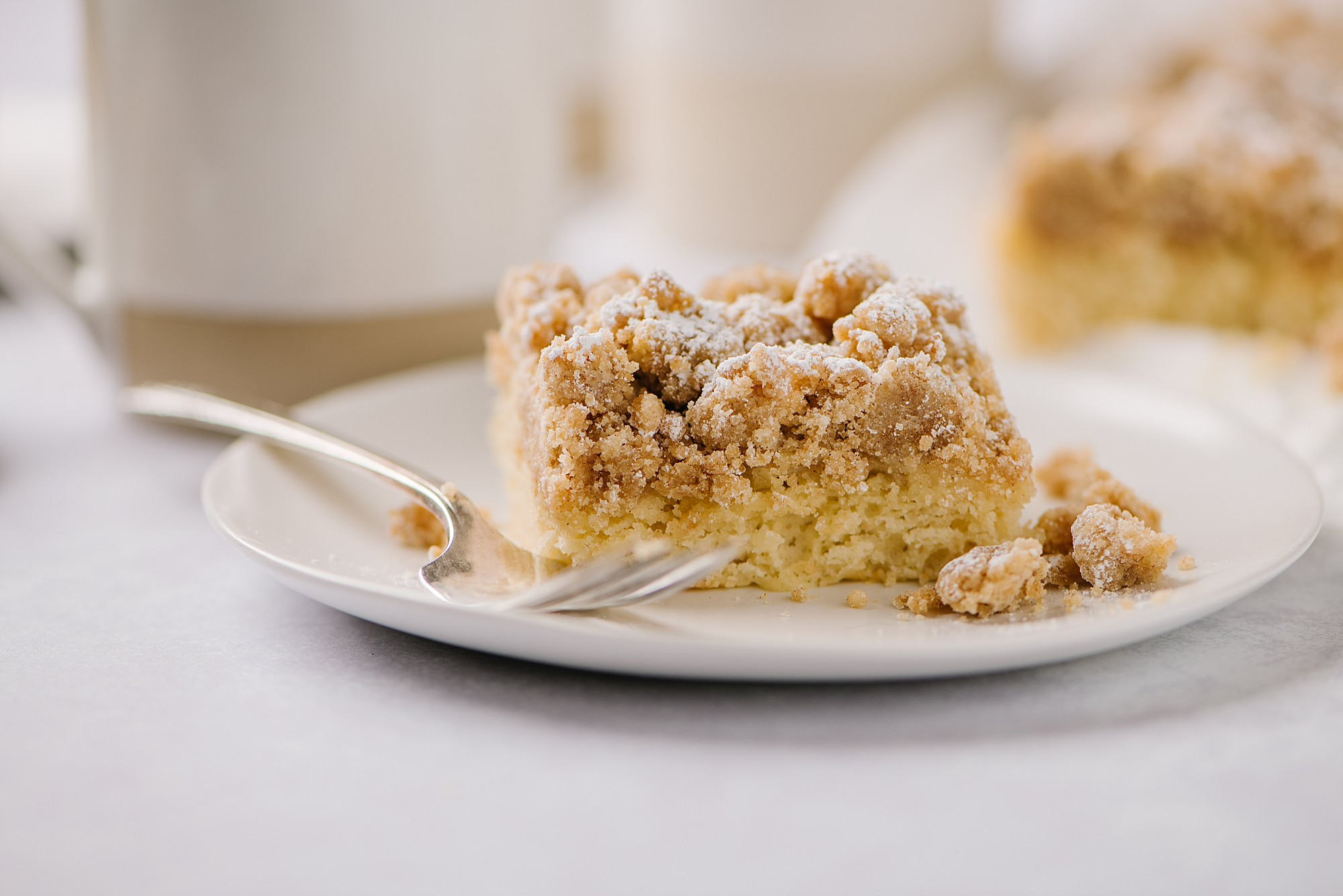 New York Style Crumb Cake on a plate with a fork and a cup of coffee in the background