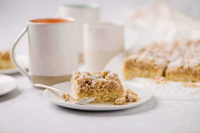 piece of cake on a plate with coffee cups