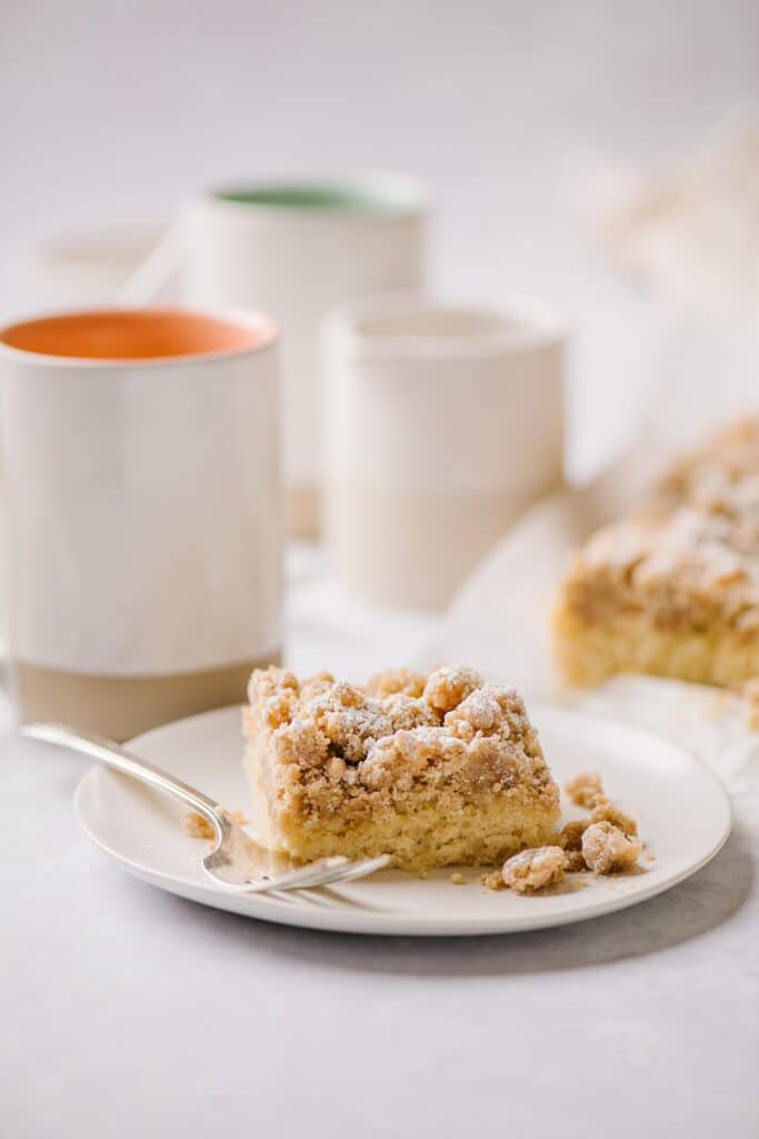 new york style crumb cake on a plate with cups of coffee in the background