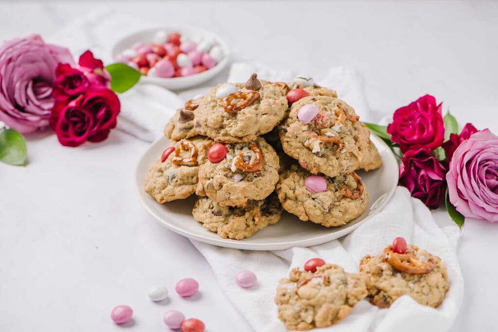 plate of Salted Peanut Butter Pretzel Cowboy Cookies with roses and a bowl of red, white, and pink, cancies in the background