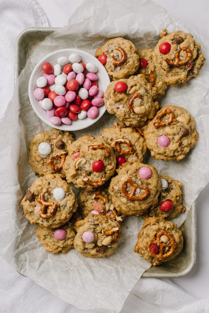 pan of Salted Peanut Butter Pretzel Cowboy Cookies with a bowl of peanut butter m&Ms on the side