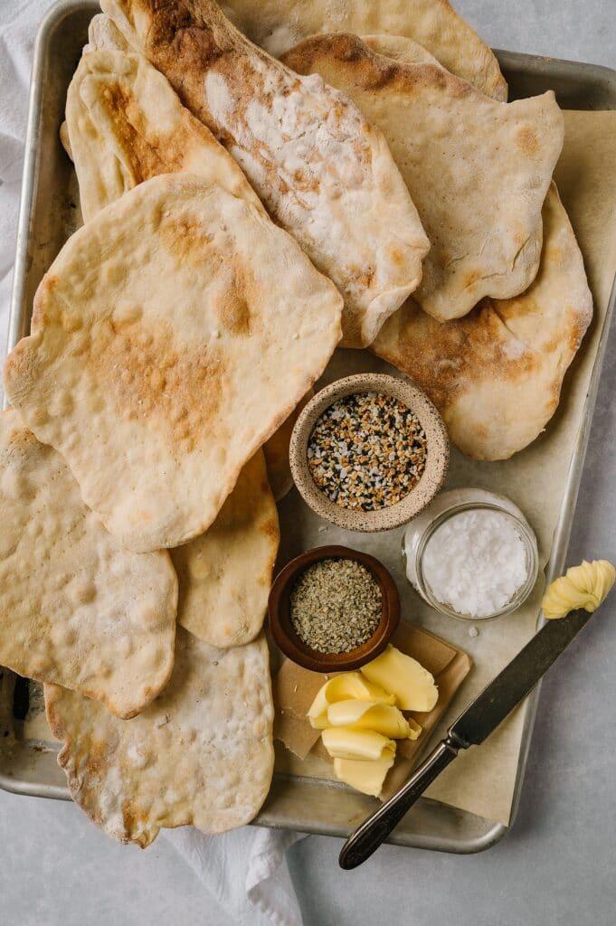 homemade matzo on a sheet pan with butter, salt, everything seasoning, and seasoned salt